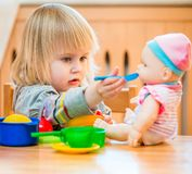 Girl feeding a doll. At home in the children's room Stock Photos