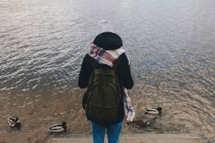 Girl feeding ducks on river , winter Stock Photos