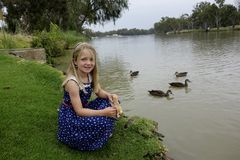Happy Young Girl Feeding Ducks By The Murray River Stock Image