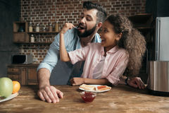 Girl feeding father with sweet jam from teaspoon. Happy girl feeding father with sweet jam from teaspoon Royalty Free Stock Photo