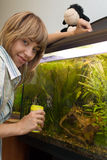 Girl feeding fish in aquarium Royalty Free Stock Image