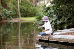 Girl feeding fish in a garden pool Royalty Free Stock Photos