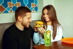 Girl feeding her boyfriend hamburger Royalty Free Stock Photo