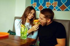 Girl feeding her boyfriend a hamburger Stock Images