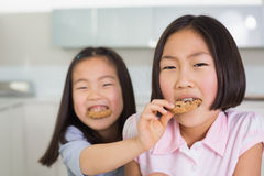 Girl feeding her elder sister a cookies in kitchen Royalty Free Stock Images