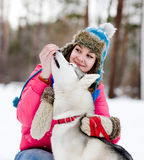 Girl feeding her husky dog Royalty Free Stock Images