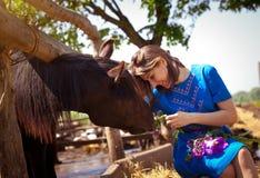 Girl is feeding a horse Stock Photo