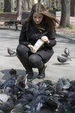Girl feeding pigeons in the park Stock Photos
