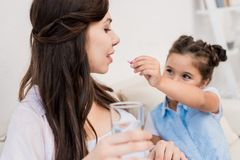 Girl feeding pill to mother. Little girl feeding a pill to her pregnant mother with a glass of water Royalty Free Stock Images