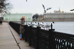 Girl feeding seagulls on the waterfront in the spring. Blonde girl feeding seagulls on the waterfront in the spring Stock Photos
