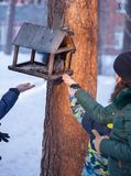 Girl feeding squirrel in the winter forest. Royalty Free Stock Images