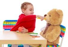 Girl feeding a Teddy bear Royalty Free Stock Images