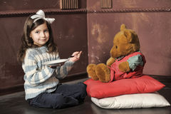 Girl feeding a teddy bear Stock Images