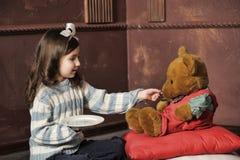 Girl feeding a teddy bear Stock Photos