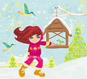 Girl feeds the birds in winter Royalty Free Stock Photo