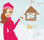Girl feeds the birds in winter Stock Photography