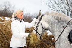 Girl feeds the horse. Stock Photos