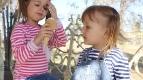 The girl feeds with ice cream the sister. In the park stock video