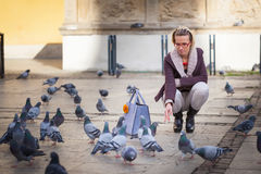 The girl feeds pigeons Stock Images