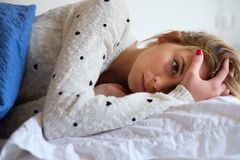 Girl feeling bad and trying to sleep. Young girl tired and lying on the bed Stock Images