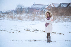 Girl is feeling cold in snow. Y field Royalty Free Stock Photography