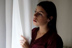 Portrait of sad young woman next to the window curtains stock image