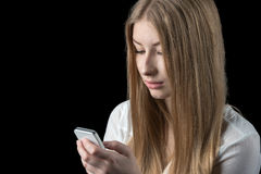 Girl feels depressed after reading bad sms on her mobile phone Royalty Free Stock Image