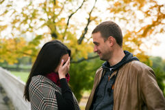 Girl feels shy. Before her boyfriend on the background of a park in a fall Royalty Free Stock Photo