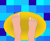 Girl feet on bath-room carpet. Beautiful feet of woman on a yellow carpet after a shower Royalty Free Stock Photos