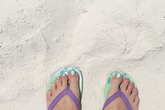 Girl feet in blue slippers on sand beach texture. Tropical seashore. Seaside banner template with text place. Summer vacation background. Coral beach sand Stock Image