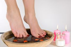 Girl feet with burgundy pedicure color in a wooden bowl with water and decoration. Decorative candles burning on floor, white background. Pedicure and spa royalty free stock photo