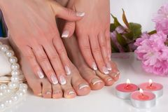 Girl feet and hands with french nail polish in spa salon with decorative pink flower, candles, pearls and towel. Young beautiful woman feet and hands with french stock photos
