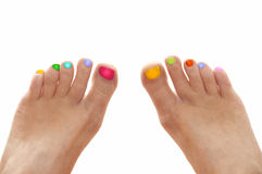 Girl feet with rainbow colorful nails isolated on white. Background Royalty Free Stock Image