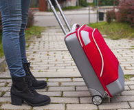 Girl feet's in jeans with near a red travel suitcase. Royalty Free Stock Photos