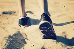 Girl feet in sneakers go away on the sand. ton Stock Photos