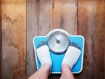 Girl feet standing on weight scale. Girl feet standing on blue weight scale over wooden floor background royalty free stock photos