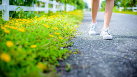 Girl feet walking on the road. Girl feet walking on the country road stock image