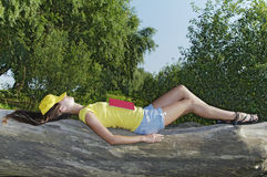 The girl fell asleep with a book. The girl fell asleep with the book. Lying on a fallen tree. Sunny Day stock photos