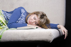 The girl fell asleep on the sofa with a book Royalty Free Stock Photography