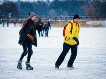 Girl and fellow ice skating in Trakai Stock Photos