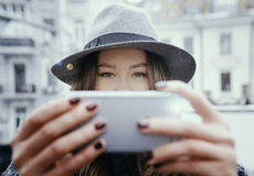 Girl in felt hat, walking around city streets, cloudy day, outdoor Stock Photo