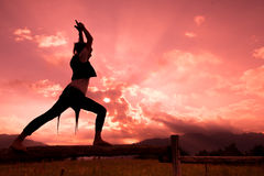 Girl on fence in nature with red sky makes gymnastics yoga movem Stock Image