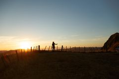 Girl by fence at sunset Stock Photography