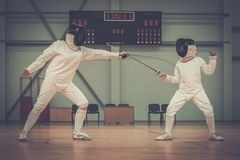 Girl fencer with trainer. Little girl fencer and her trainer royalty free stock photo