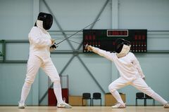 Girl fencer and with trainer. Little girl fencer and her trainer royalty free stock photo