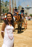 Girl in Feria Dress with Horse and Carriage. Spanish girl in traditional dress with adorned horse drawn carriage in background. Midday sun overhead. Andalusia royalty free stock images