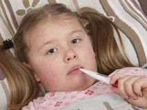 Girl with fever. Little girl laying in bed with fever Stock Images