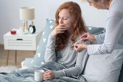 Girl with fever in bed. Grandmother taking care of a girl with fever lying in bed and drinking tea Royalty Free Stock Image