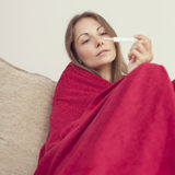 Girl with fever. Young woman sitting on a couch covered with blanket, having a fever, holding a thermometer after measuring temperature Stock Image