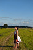 Girl in field. Girl stand at the path in field and look to You! She is smiling to you, and wind blows about her hairs Royalty Free Stock Photo